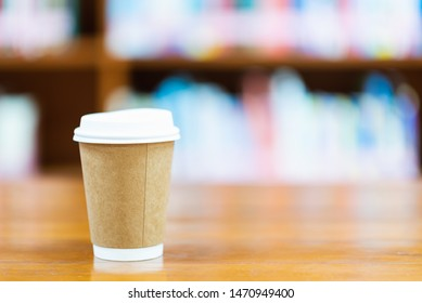 Brown paper coffee cup set on a wooden table in the library
