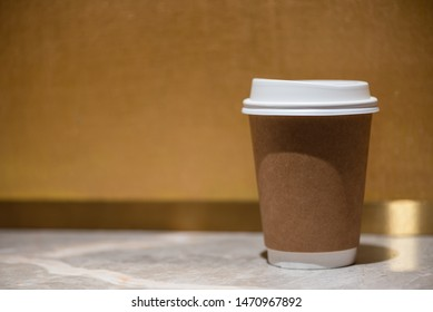 Brown paper coffee cup set on marble floor, on a golden background.
