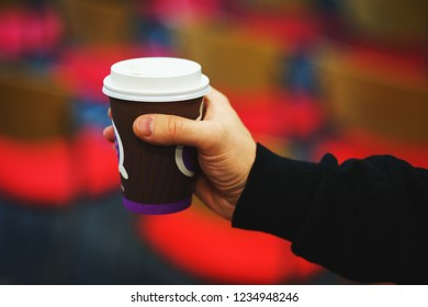 Brown paper cup in hand. Student, office worker holding a plastic paper cup in the audience. A young man drinks tea from a cup of coffee. Soft focus.