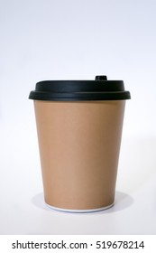 The brown paper cup of hot coffee with black cap.