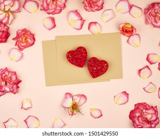brown paper envelopes and two red carved hearts in the middle of rosebuds, top view, festive backdrop