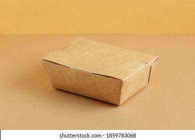 Brown paper food box. Ground color background. Reusable package concept