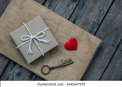 Brown paper gift box tie with rope decorated with red mini heart on old wooden background, valentine's day present concept, copy space