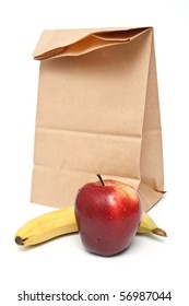 Brown paper lunch bag with red apple and banana on white background