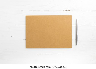 brown paper with pen on white table view from above
