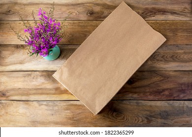 Brown paper shopping bag mockup with purple wildflowers. Kraft recycled grocery shopping bag mock up for branding presentation.
