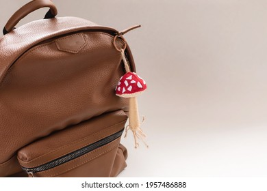 Brown part leather backpack with a mushroom-shaped keychain. The concept of travel, vacation, road, school education.