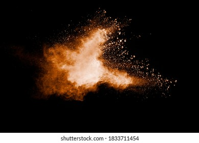Brown particles splattered on black background. Brown dust splashing.