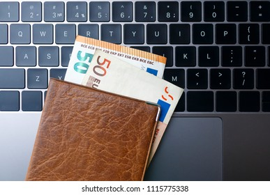 brown passport with euro banknotes on the opened gray laptop