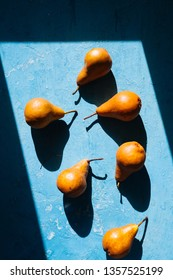 Brown  pears on blue concrete background from above