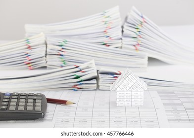 Brown pencil with calculator and house on finance account have blur pile overload paperwork of report and receipt with colorful paperclip place on white background. Business finance concept success.
