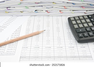 Brown pencil and calculator on finance account with pile of paperwork as background. Stack of paperwork is high as work hard. Business and finance concepts rich and successful photography.