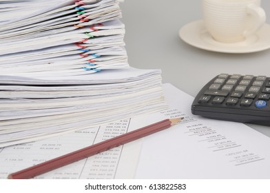 Brown pencil and calculator on finance account have blur pile overload document of report and receipt with colorful paperclip and cup of coffee as background. Business and finance concept photography.