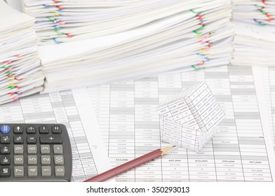 Brown pencil and house on finance account have calculator and pile of document as background. Stack of paperwork is high as work hard. Business and finance concepts rich and successful photography.