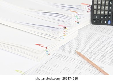 Brown pencil on finance account have calculator and step pile of paperwork as background. Stack of paperwork is high as work hard. Business and finance concepts photography.
