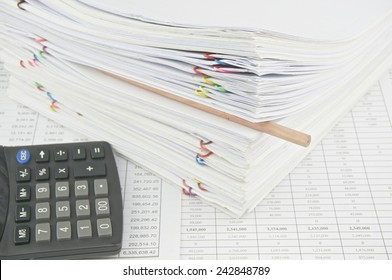 Brown pencil put in stack paperwork with calculator on finance account. Stack of paperwork is high as work hard. Business and finance concepts rich and successful photography.