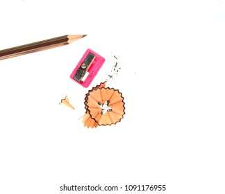 Brown Pencil pencil sharpener and pencil scraps on white background.