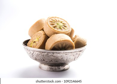 Brown Pera or pedha is an indian sweet made using  khoa, sugar and traditional flavorings, including cardamom seeds, pistachio nuts. served in a bowl or plate. selective focus