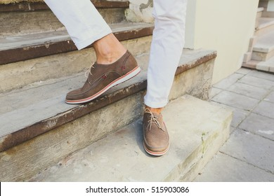 Brown perforated suede summer shoes with laces. Man in white trousers on the steps in the city. Men's summer fashion, stylish men's shoes.