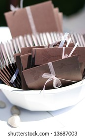 brown and pink wedding programs organized neatly in a bowl for the guests