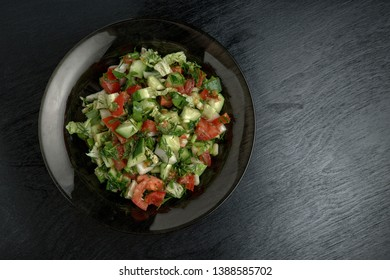 Brown plate with salad on dark background. Top view