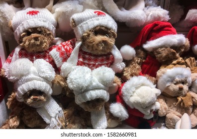 Brown plush teddy bears in white and  red Christmas caps with pompons and red-white sweaters and white scarfs.