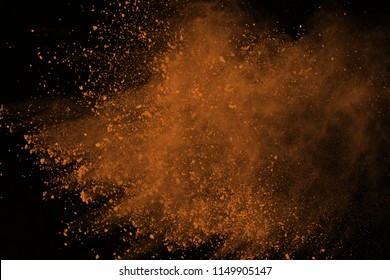 Brown powder explosion isolated on black background. Colored dust splatted.