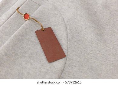 Brown Rectangular Tag on the Grey Sweatshirt from Footer