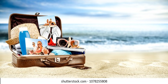Brown retro suitcase on beach and sea landscape. Free space for your decoration.