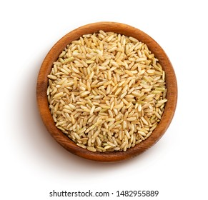 Brown rice groats in wooden bowl isolated on white background, top view