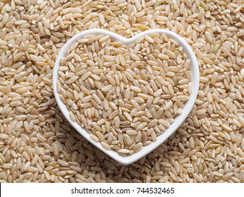Brown rice in heart-shaped bowl on rice background. Copy space. Top view or flat lay.