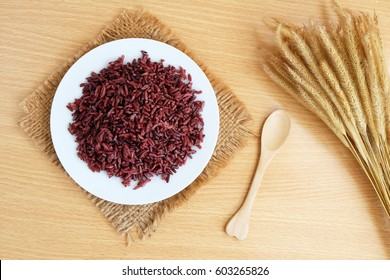 Brown rice on wooden background.