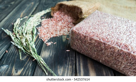 brown rice pack in vacuum plastic bag and paddy on black wood