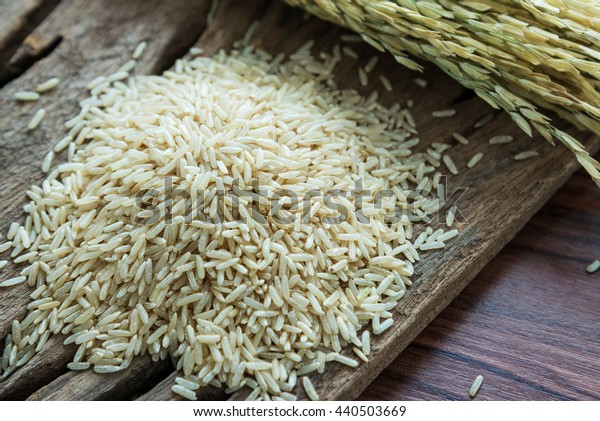 brown rice pile with rice plants on a dark wooden table