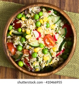 Brown rice salad with cherry tomato, corn, cucumber, radish, pea and chives served in bowl, photographed overhead on dark wood with natural light (Selective Focus, Focus on the top of the salad)