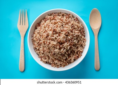 Brown Rice/Coarse rice with wooden spoon and fork on pastel blue background. Top view.
