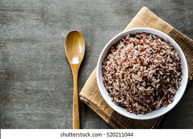 Brown rice/Coarse rice with wooden spoon. Top view.