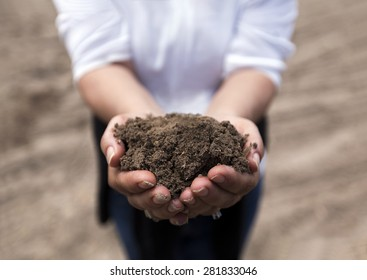 Brown rich soil in hands from agricultural area