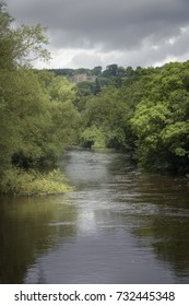 The brown river Wharfe in moody atmosphere and green and castle background