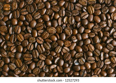 Brown roasted coffee beans laying on table texture