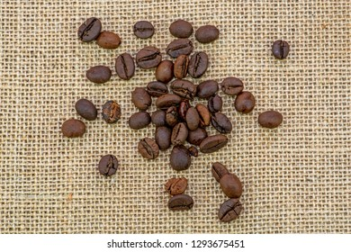 Brown roasted coffee beans on the sackcloth background, heap of roasted coffee beans on sackcloth close up. Top view