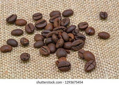 Brown roasted coffee beans on the sackcloth background, heap of roasted coffee beans on sackcloth close up