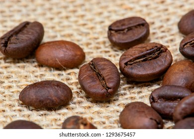 Brown roasted coffee beans on the sackcloth background, heap of roasted coffee beans on sackcloth close up. Shallow depth of field, selective focus, artistic bokeh, blurred background