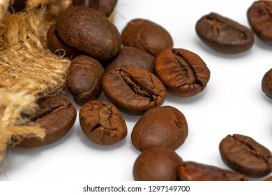 Brown roasted coffee beans with the sackcloth, heap of roasted coffee beans with sackcloth close up on white background