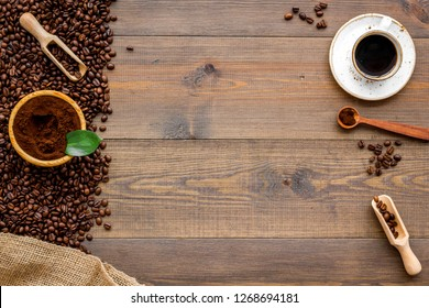 Brown roasted coffee beans scattered on wooden background and cup of americano top view mockup