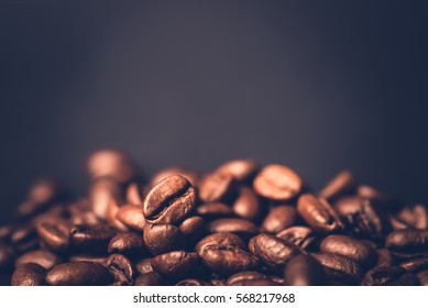 Brown roasted coffee beans, seed on dark background. Espresso dark, aroma, black caffeine drink. Closeup isolated energy mocha, cappuccino ingredient.