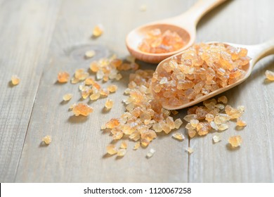 Brown rock sugar on wood spoon and on old wood background,
