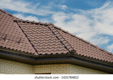 Brown roof of ceramic tiles and blue sky with beautiful clouds.