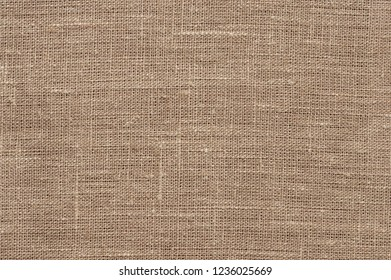 Brown rough linen fabric texture close-up as background.