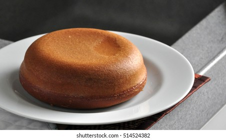 Brown and round cake made from rice cooker on white plate.